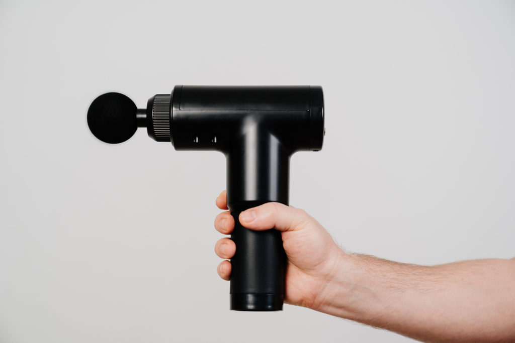 men's hands holds massage gun. medical-sports device helps to reduce muscle pain after training, helps to relieve fatigue, affects problem areas of body, improves condition of skin.